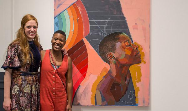 Two Women stand in front of Trustman Exhibit piece