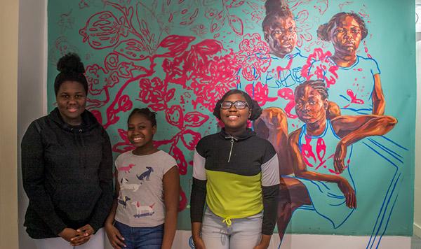 Three Children stand in front of Trustman Exhibit piece