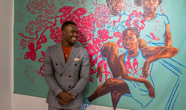 Man stands in front of Trustman Exhibit piece