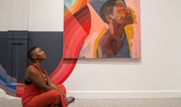Womans sits in front of Trustman Exhibit piece